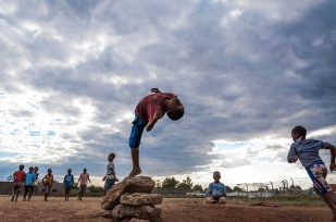 An unidentified group of young boys play backflips in Cateme, Tete / Mozambique. The country has a young population with the proportion of children below the age of 15 in 2010 was 44.1%.